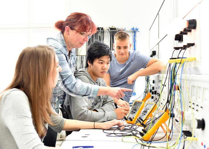 En kvinnlig lärare pekar på utrustning som tre ungdomar. Utrustningen är för att mäta elektricitet.